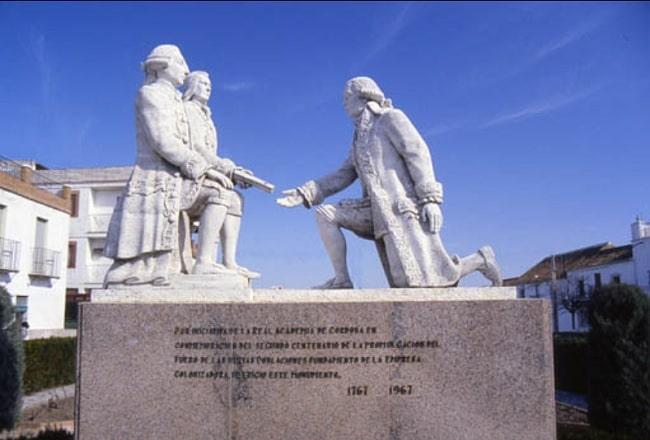 Monumento en el que se ve a Pablo de Olavide, arrodillado, recibiendo de Carlos III, en presencia de Campomanes, las órdenes reales para la colonización de Sierra Morena con las Nuevas Poblaciones