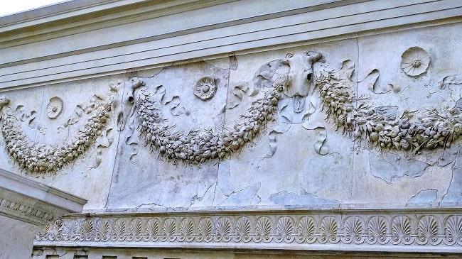 Vista detallada de los relieves de guirnaldas y bucráneos que decoran las paredes del interior del altar de la paz augustea